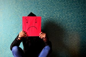 A young person indicates their unhappiness with a sad face drawn on a piece of paper in front of their face