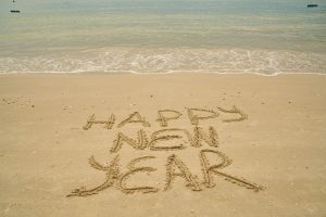 Happy new year written in the sand on a beach